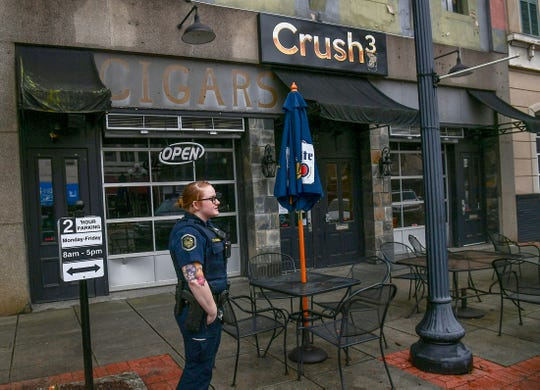 Anderson officer T.R. Tucker stands outside a closed Crush3 bar monitoring traffic on North Main Street in downtown Anderson as many restaurants are preparing for bake and takeout meals Tuesday, March 17, 2020.