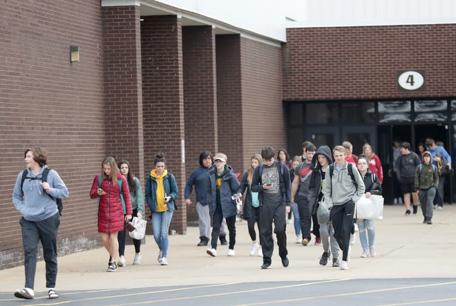 Students leave Neenah High School before the school district transitioned to online learning to prevent the spread of COVID-19.