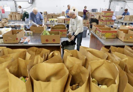 Volunteers pack bags for curbside pickup at St. Joseph Food Program on Tuesday in Menasha.
