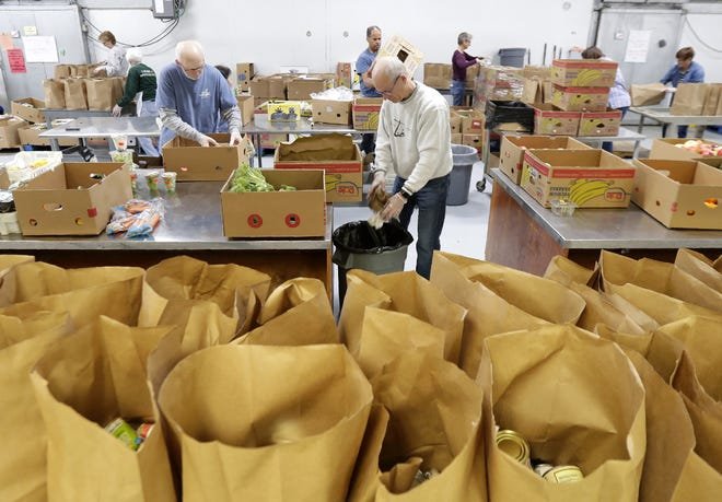 Volunteers pack bags for curbside pickup at St. Joseph Food Program on Tuesday in Menasha.