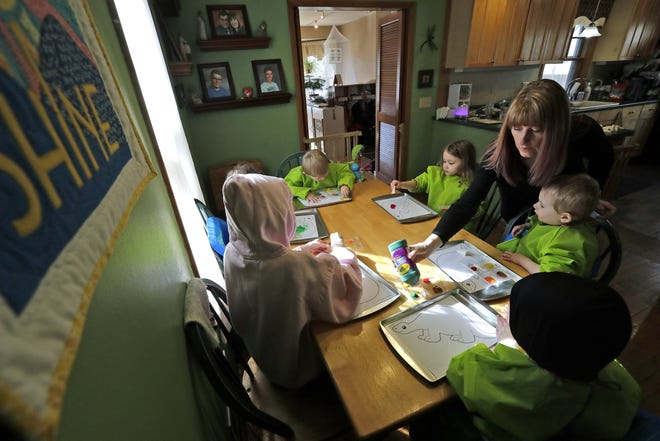 Day care provider Amy Nogar keeps children entertained by giving them an art project to work on Tuesday at her home in Appleton.
