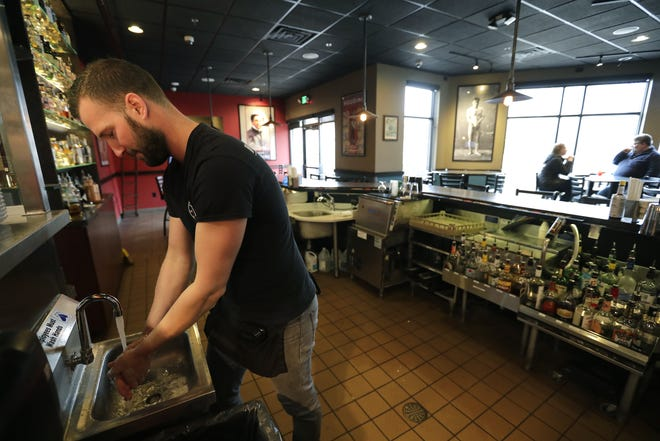 Houdini's Escape Gastropub employee Terry Lagarde washes his hands before taking a dine-in lunch order from customers on Monday. As of Tuesday, the restaurant closed its dining room, but offered its full menu through phone orders and curb-side pick-up.