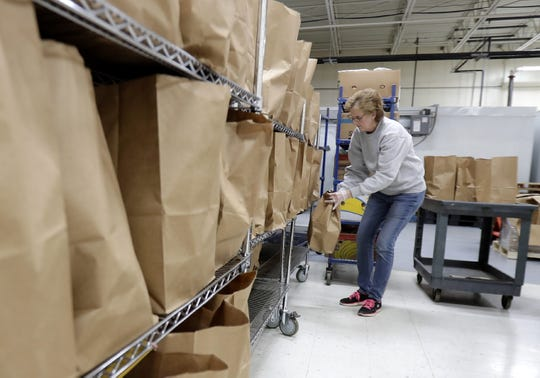 Volunteer Sharon Rassel stacks packed bags of food for curbside pickup at St. Joseph Food Program on Tuesday in Menasha.