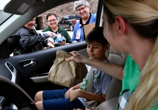 Kristi Rodriguez takes the sack lunches being handed out Tuesday by Student Nutrition workers at Johnston Elementary School. Rodriguez was feeding her 9-year-old son Lucas and two other children in the back seat. The Abilene Independent School District is handing out breakfast and lunch to students at designated schools.