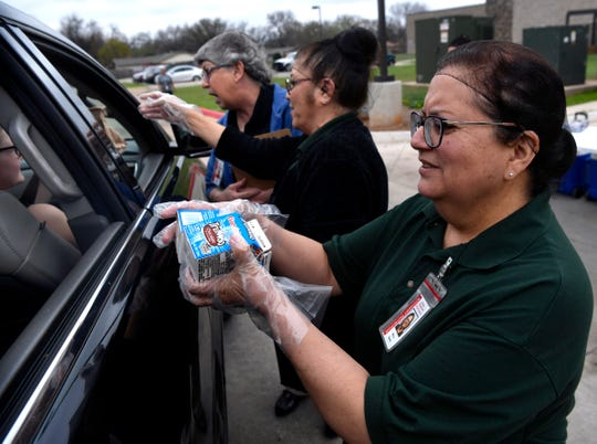 Melba Guerra hands chocolate milk to children sitting in the back seat of an SUV at Johnston Elementary School. Parents, and some students, came to the back of the school to pick up their lunches.