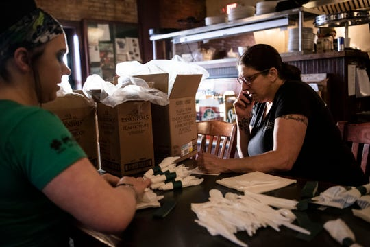 Alex Hawkins and Connie Jones take and assemble orders for carryout at Griffin Grill & Pub on Tuesday, March 17, 2020 during St. Patrick's Day in Battle Creek, Mich. Michigan Gov. Gretchen Whitmer called for all bars and restaurants to close statewide at 3 p.m. on Monday to limit the spread of COVID-19.