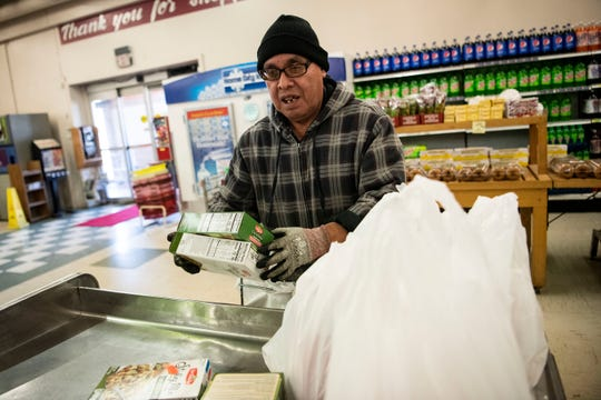 Grocer Victor Lopez bags groceries at Main Street Market on Tuesday, March 17, 2020 in Battle Creek, Mich.