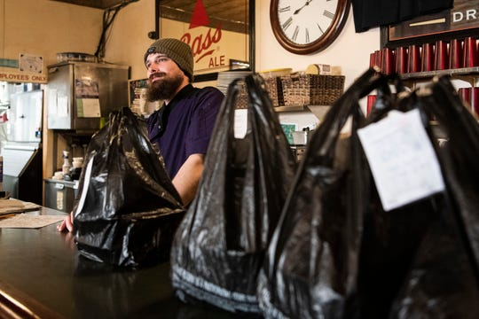 Wyatt Butler assembles takeout orders at Griffin Grill & Pub on Tuesday, March 17, 2020 during St. Patrick's Day in Battle Creek, Mich. Michigan Gov. Gretchen Whitmer called for all bars and restaurants to close statewide at 3 p.m. on Monday to limit the spread of COVID-19.