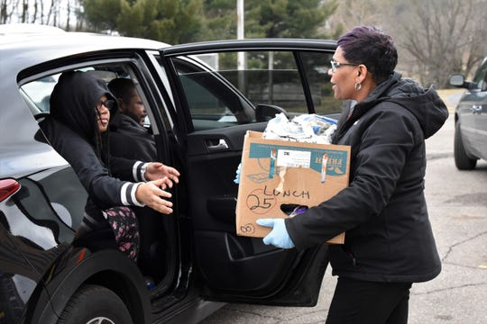 Zena Perry, site coordinator for Communities in Schools, delivers food to a student outside of Dudley Elementary on Tuesday, March 17, 2020.