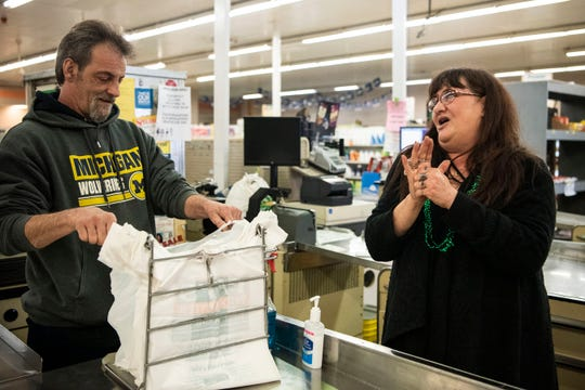 Judy Russell sanitizes her hands as Joe Johnson begins his shift at Main Street Market on Tuesday, March 17, 2020 in Battle Creek, Mich.