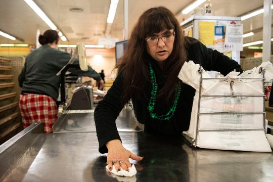Grocer Judy Russell sanitizes the counter between each customer at Main Street Market on Tuesday, March 17, 2020 in Battle Creek, Mich.