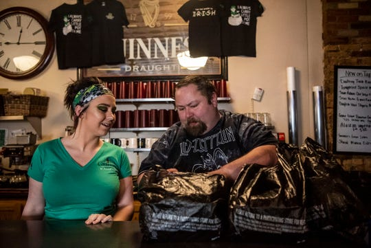 Alex Hawkins and Richard Foote assemble takeout orders at Griffin Grill & Pub on Tuesday, March 17, 2020 during St. Patrick's Day in Battle Creek, Mich. Michigan Gov. Gretchen Whitmer called for all bars and restaurants to close statewide at 3 p.m. on Monday to limit the spread of COVID-19.