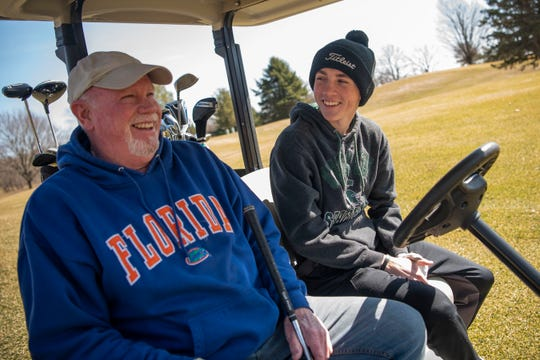 Steve Sharron shares a laugh with his grandson Ty Peete, 14, at Binder Park Golf Course on Tuesday, March 17, 2020 in Battle Creek, Mich. As sports come to a halt in Michigan to limit the spread of COVID-19, golf courses remain open.