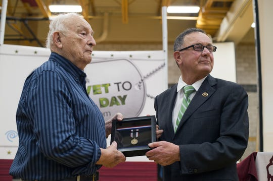 ANDREW THAYER / Staff Photo Left, World War II veteran Edward Knowlden is presented a Prisoner of War Medal by U.S. Rep. Richard Hanna during a veterans event Tuesday at Johnson City Middle School. World War II veteran Edward Knowlden, left, is presented a Prisoner of War Medal by Rep. Richard Hanna during a a veterans event Tuesday at Johnson City Middle School.