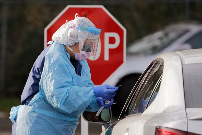Theresa Malijan, a registered nurse, completes taking a nasopharyngeal swab from a patient at a drive-through COVID-19 testing station for University of Washington Medicine patients on Tuesday, March 17, 2020, in Seattle. The appointment-only drive-through clinic began a day earlier. Washington leads the country in the number of deaths, with most being associated with a nursing home in Kirkland. By Monday, the number of positive cases topped 900.