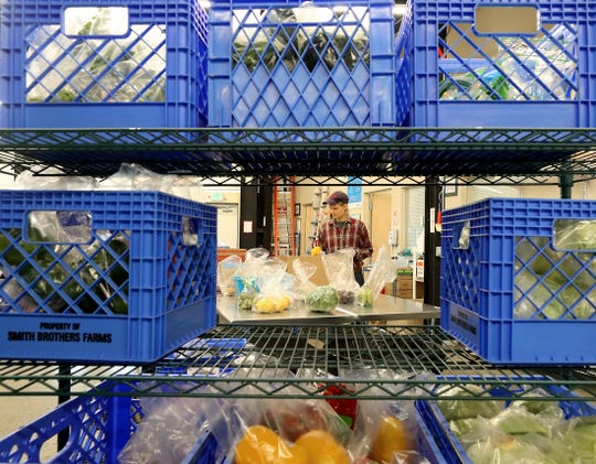 Homeshare coordinator Emily Klein is framed by crates of vegatbles as she sorts produce into individual ready-to-go bags for distribution at North Kitsap Fishline in Poulsbo on Tuesday, March 17, 2020.