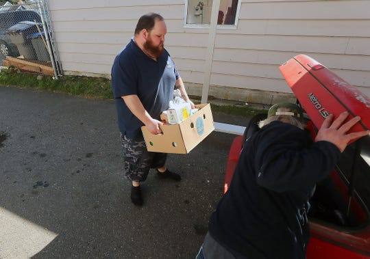 Volunteer Isaac Stargel prepares to place a box of provisions inside an open trunk at the Saint Vincent de Paul food bank in Bremerton on Monday. The food bank has been running a drive-thru pickup line in response to the spread of coronavirus.