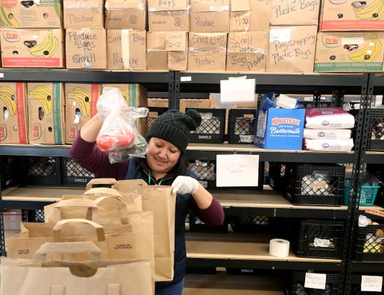 Volunteer coordinator Lidia Gamero packs a pick-up order of food and goods at North Kitsap Fishline in Poulsbo on Tuesday, March 17, 2020.