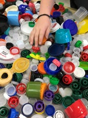 Students at Ocean Breeze Elementary gather and send in recyclable plastic caps and lids to ABC Promise in Indiana, which turns the caps into a bench for the school.
