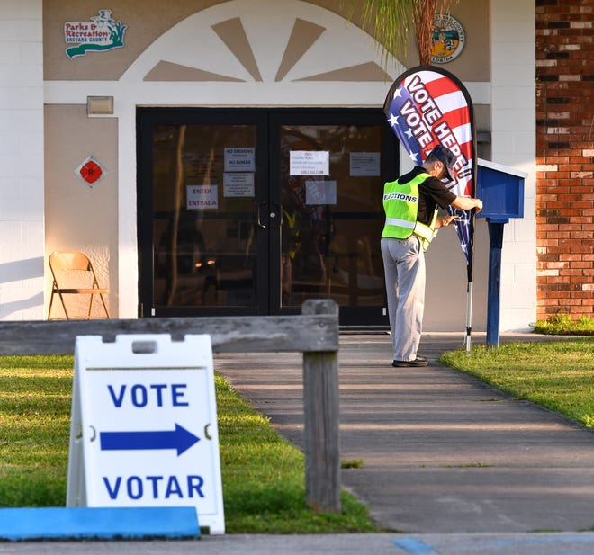 A poll deputy fixes the Vote Here sign at McClarty Park in Rockledge in Brevard County. Tuesday was Primary Day in Florida with Republicans and Democrats getting to cast their vote.