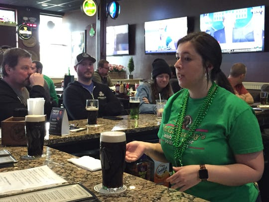 Nicole Broderick waits on customers at McGillicuddy's Irish Ale House in Williston on March 17, 2020, less than two hours before a state-mandated closure of bars and restaurants takes effect because of the COVID-19 outbreak.