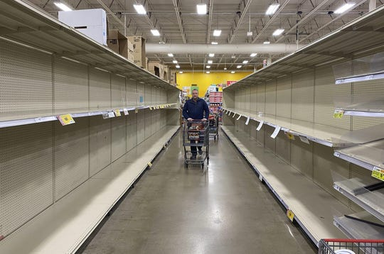 Customers at grocery chain HEB in Austin look for products among increasingly empty shelves as the city responds to concerns of the spread of the new coronavirus and COVID-19.