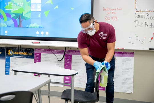 Ed Mapue sanitize a classroom at Atkins Middle School on Tuesday, March 17, 2020. The district is performing a deep cleaning of all campuses and once completed schools will not allow anyone to enter until classes resume.