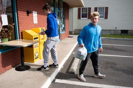 Shawn Weller, right, and his friend Mikey Olsen pickup an order from the Westmont Diner as they remain open for takeout and delivery Tuesday, March 17, 2020 in Haddon Township, N.J.