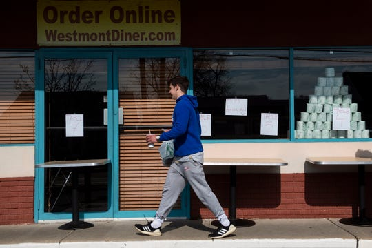 Mikey Olsen, 16, picks up an order from the Westmont Diner as they remain open for takeout and delivery Tuesday, March 17, 2020 in Haddon Township, N.J.