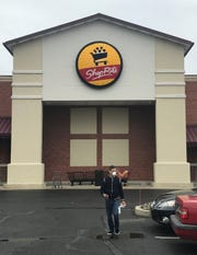 A masked shopper returns to his car outside a ShopRite supermarket in Cherry Hill Tuesday.