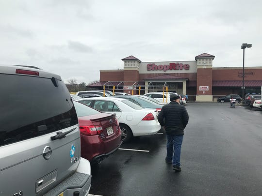 A shopper treks through the crowded parking lot outside a ShopRite store off Route 70 in Cherry Hill.