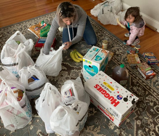 Jessica Bruner sorts groceries and toiletry items that her husband's company, American Construction of Cherry Hill, bought to  distribute to help needy S. Jersey families during the COVID-19 pandemic.