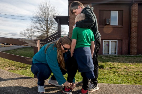 Michelle Hicks, ties the shoe of her son, Jason, 6, as his brother, Zyah, 11, embraces him as they prepare to leave New Richmond Childcare on Tuesday, March 17, 2020, in New Richmond. Both Zyah and Jason have been attending New Richmond Childcare during school hours since schools went to distance learning in Ohio.