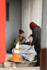Scarlet Hudson, pastor and founder of Women of Alabaster, right, hands food and a hygiene kit to a woman who lives on the streets in East Price Hill, Tuesday, March 17, 2020. Hudson runs a day minister for human trafficking victims. Due to the new coronavirus, she and her team took to the streets to bring food and outreach to people who didn't have access to basic needs.