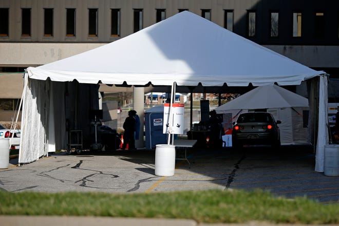 Patients drive through triage tents set up near the Hoxworth Blood Center in the Avondale neighborhood of Cincinnati on Tuesday, March 17, 2020. Tents have been open to provide drive-through service and testing for the novel coronavirus.