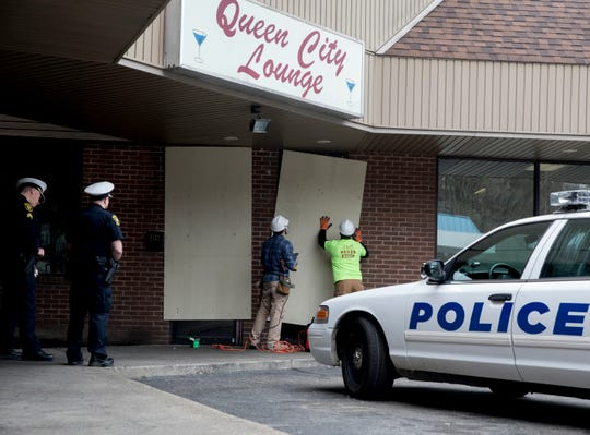 Workers board up Queen City Lounge on Tuesday, March 17, 2020, in Cincinnati. Police said Queen City Lounge had violated Governor DeWine's order banning gatherings of more than 50 people and would be boarded up after ignoring a warning to close from police.