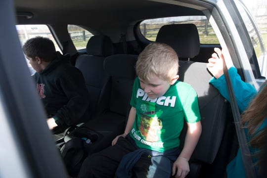 Michelle Hicks, picks up her sons Zyah, 11, and Jason, 6, from New Richmond Childcare on Tuesday, March 17, 2020, in New Richmond. Both Zyah and Jason have been attending the day care all day since schools went to distance learning.