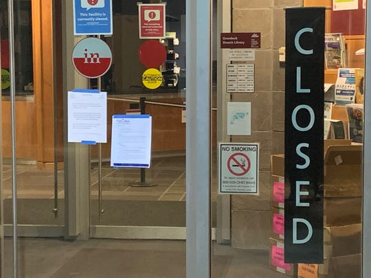 Notices that Ohio's primary is postponed are taped to the entrance of the Cincinnati Public Library branch in Groesbeck early Tuesday morning, March 17.