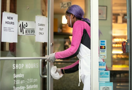Timeka Smith said she's a little nervous, but trying not to panic as she works the counter at Hultman's Donuts in Over-the-Rhine. She said she's wearing gloves and continually cleaning counters, doorknobs and other things, Tuesday, March 17, 2020.