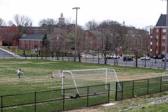 A sole student practices kicking soccer balls into a goal with the recreation field to himself on Austin Peay State University's campus in Clarksville, Tenn., on Friday, March 13, 2020.