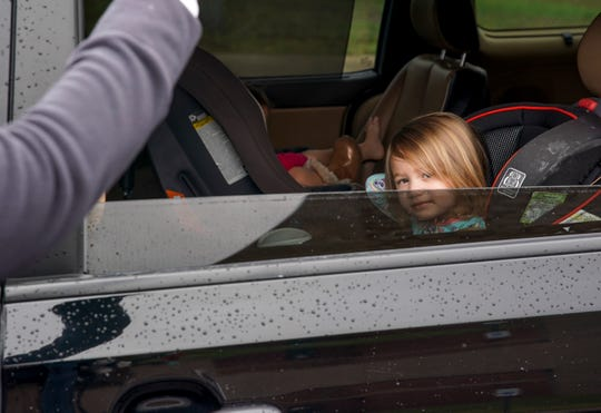 Audrey Hutcherson, 3, peers out the back window of the family minivan as cafeteria workers hand out meals at Kenwood High School in Clarksville, Tenn., on Tuesday, March 17, 2020.