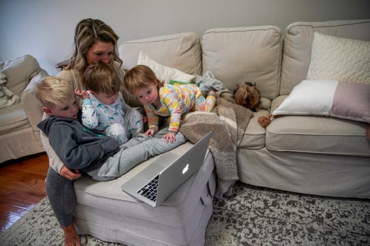 Chelsea Farley holds her children Cannon, 4, left, Asher, 2, center, and Charleston, 1, right, while watching a live stream where Maj. Gen. Brian Winksi and others from Fort Campbell address the spread of COVID-19 coronavirus and their response at the Farley household in Clarksville, Tenn., on Monday, March 16, 2020.