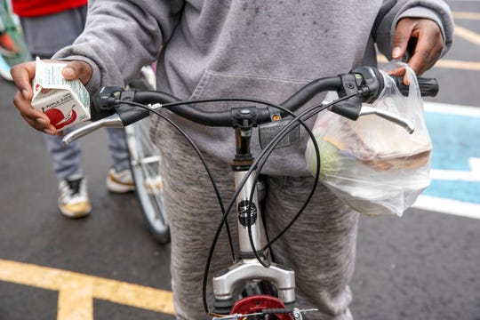 Q'vonte Jumper, 11, fits his bagged lunch onto his handle bar and holds apple juice in the other hand when he and a group of friends rode to school to grab lunch together at Kenwood High School in Clarksville, Tenn., on Tuesday, March 17, 2020.