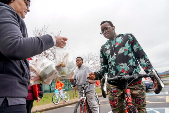 Adrian Dunlap, 16, grabs a bagged lunch from Kerstin Milledge, left, when he rode to school to grab a meal during a week where all CMCSS schools were closed at Kenwood High School in Clarksville, Tenn., on Tuesday, March 17, 2020.