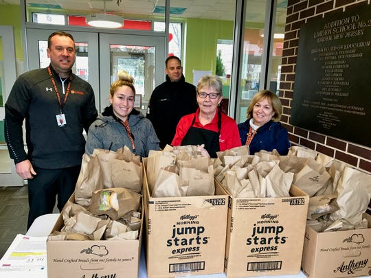 Bagged lunches awaited pick-up by students at School No. 2 in Linden on Tuesday, the first day of at-home learning. From left are Acting Assistant Superintendent Michael Walters, School No. 2 paraprofessional Jackie Freire, Linden Police Department Special Law Enforcement Officer Class III George Allard, Kathy Kuchie of Pomptonian Food Service, and School No. 2 secretary Fernanda Freire.