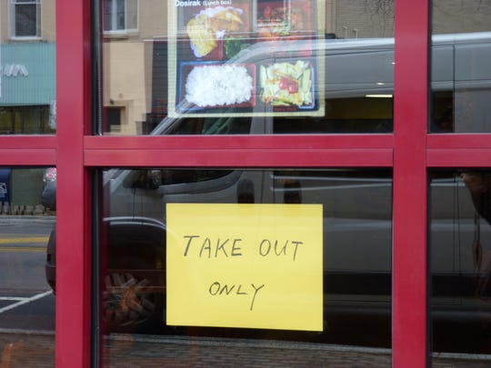 A sign at a restaurant in downtown Somerville offering take-out only during the coronavirus pandemic.