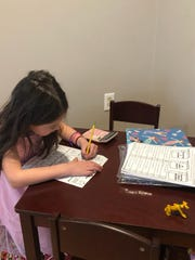 Cece Vignola, 6, a first grader at Lester D Wilson School in Alexandria, is hard at work remote learning at home during the COVID-19 pandemic.