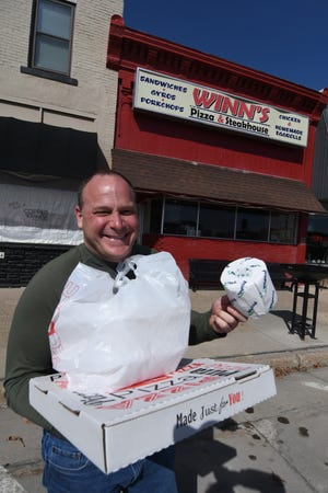 Brad Kotz of Indianola walks out of Winn's Pizza and Steakhouse in Indianola with his carryout food order and a roll of toilet paper on March 17. Following Gov. Kim Reynolds calling for restaurants to close for inside dining during the coronavirus outbreak, Winn's was open for carryout only and giving away a roll of toilet paper with every $25 spent.