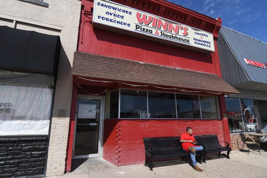 Matthew Say, who works at Winn's Pizza and Steakhouse in Indianola, sits outside the restaurant on March 17. The business was open for carryout only after Gov. Kim Reynolds called for restaurants to close for inside dining during the coronavirus outbreak.