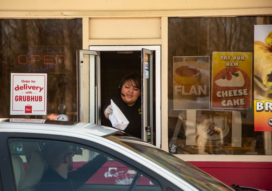 Miriam Erbantes works the drive-thru window at Abelardo's Mexican Restaurant in Des Moines Tuesday, March 17, 2020.
